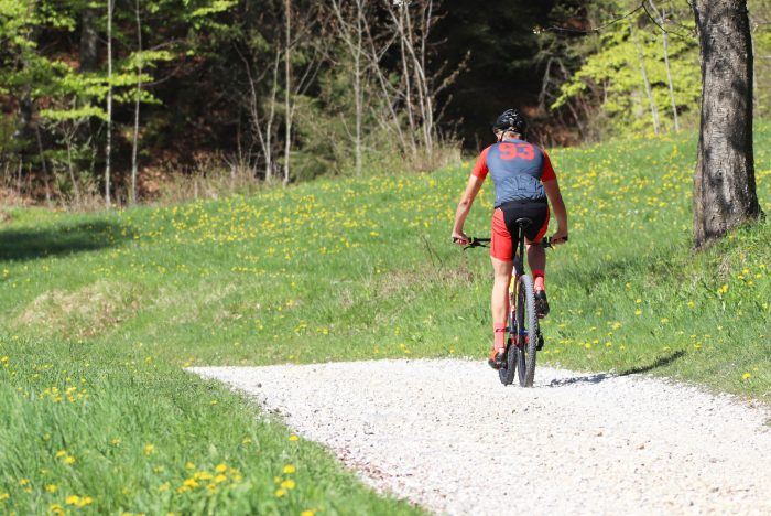 """Mountainbiker mit DOWE Sportswear Race/Allround Bikeshort """"Passion Red"""" im Grünen"""