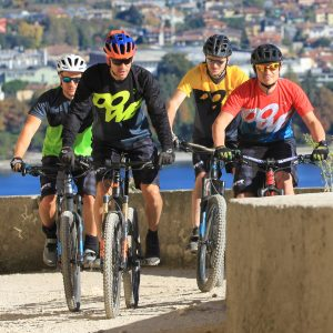 Four male mountain bikers wearing DOWE Sportswear shorts and jerseys