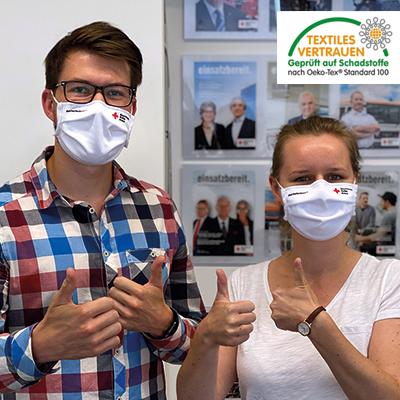 Zwei Erwachsene tragen Dowe Community Mask Basic und zeigen die Daumen - mit Textiles Vertrauen Logo